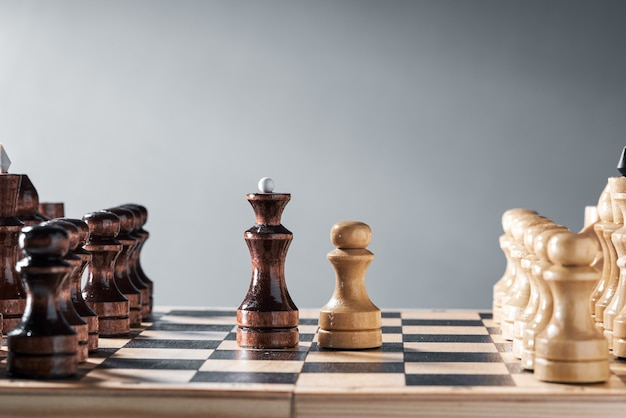 Wooden chess pieces on a chessboard, the confrontation of the white pawn and the black queen, planning and decision-making concept