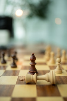 Wooden chess pieces on a chessboard, leadership concept