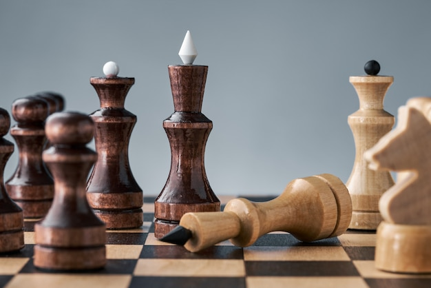 Wooden chess pieces on a chessboard, the white king lies in front of the black pieces, the concept of strategy, planning and decision making