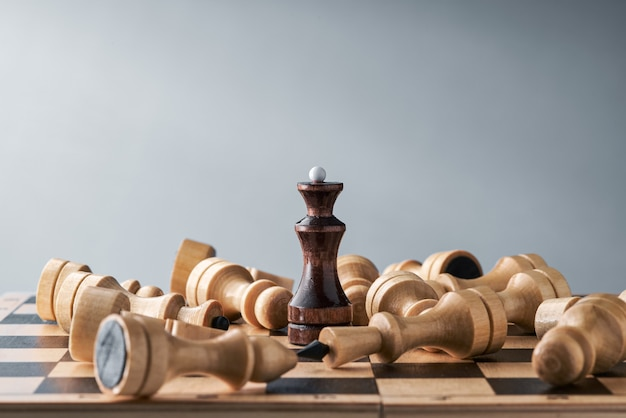 Wooden chess pieces on a chessboard, white pieces lie around the black queen, the concept of strategy, planning and decision making