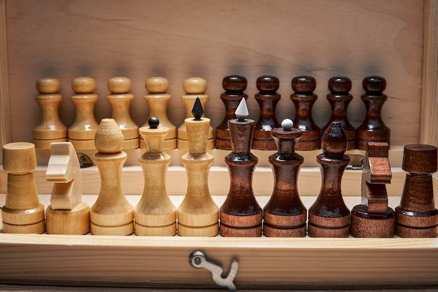 Деревянные шахматные фигуры в шахматной коробке, основные фигуры на переднем плане, пешки на заднем плане, концепция, стратегия, планирование и принятие решений