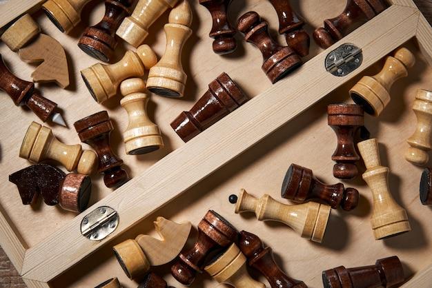 Деревянные шахматные фигуры лежат в открытом ящике для шахмат, стратегии, планирования и принятия решений.