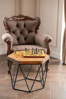 Деревянные шахматные фигуры на настольной игре, на винтажном столе на фоне стула, выборочный фокус.