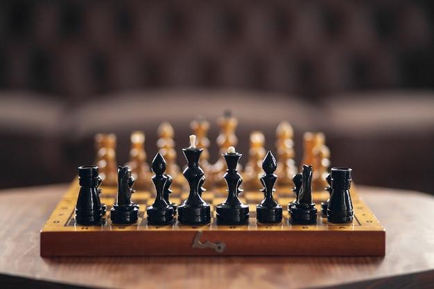 Деревянные шахматные фигуры на настольной игре, на винтажном столе, выборочный фокус.