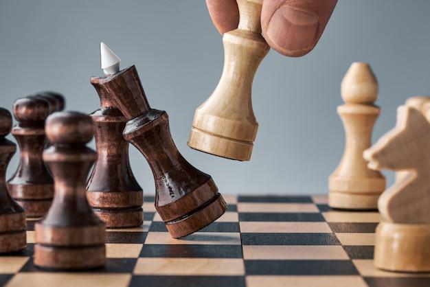 Деревянные шахматные фигуры на шахматной доске, рука с белым ферзем делает ход, концепция стратегии, планирования и принятия решений