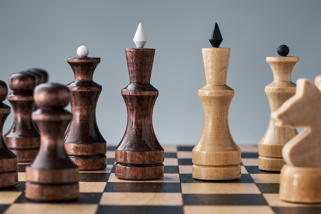 Деревянные шахматные фигуры на шахматной доске, противостояние белого и черного королей, концепция стратегии, планирования и принятия решений