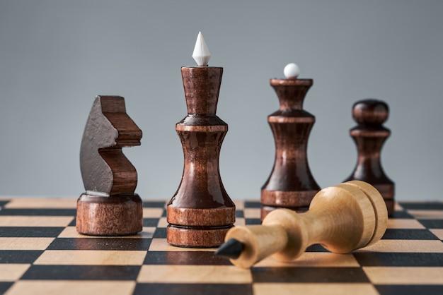 Деревянные шахматные фигуры на шахматной доске, белый король лежит перед черными фигурами, концепция стратегии, планирования и принятия решений