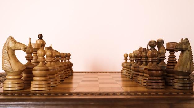 Деревянная шахматная доска с деревянными коричневыми шахматными фигурами.
