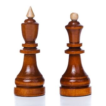 白い背景で隔離の木製のチェスの駒。キングとクイーンのチェスの駒