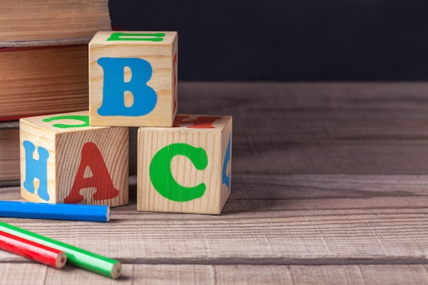 Wooden children's blocks with letters and colored pencils close-up, lie on a wooden table