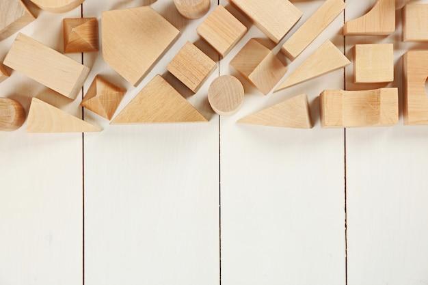 Деревянные детские кубики на белом деревянном фоне