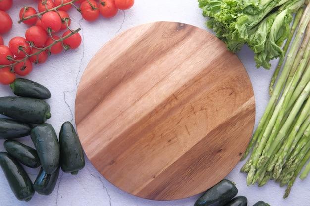 Деревянная разделочная доска и свежие овощи на столе сверху вниз