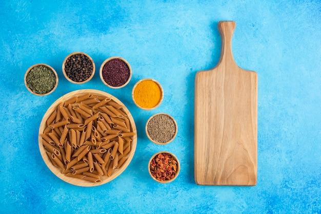 木製のまな板と青い背景の上のスパイスと生の茶色のパスタ。