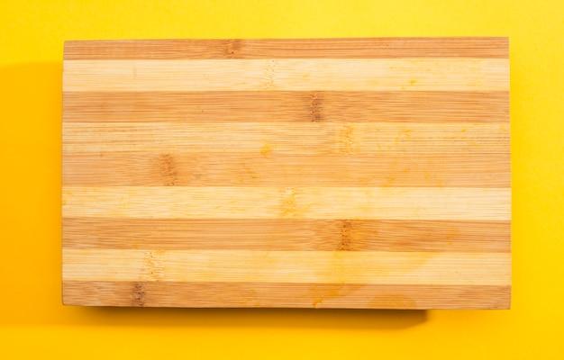 黄色の背景に木製のまな板