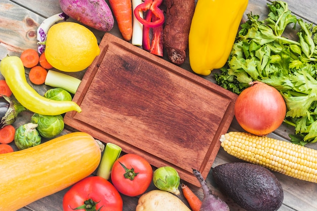Wooden chopping board surrounded by various raw food