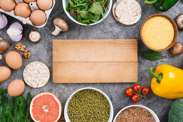 Wooden chopping board surrounded with ingredients on concrete backdrop
