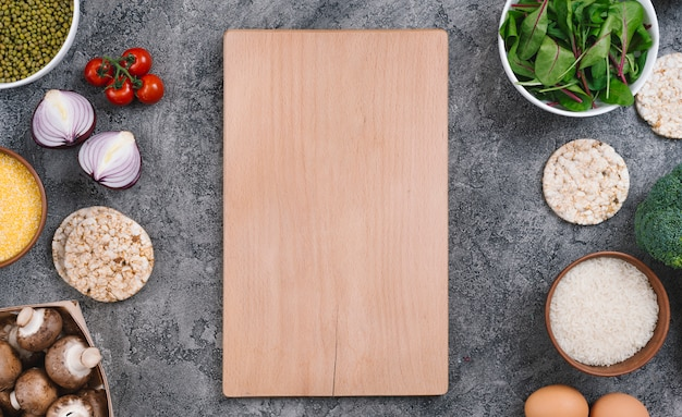 Wooden chopping board surrounded with vegetables and puffed rice cakes on concrete backdrop