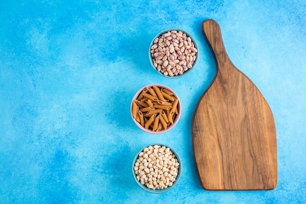 Wooden chopping board and three bowl full with raw pasta and beans over grey surface.