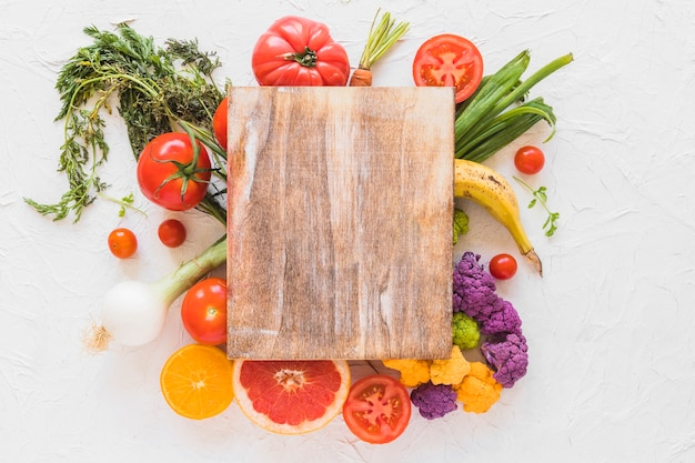 Wooden chopping board over the vegetables and fruits on white texture backdrop
