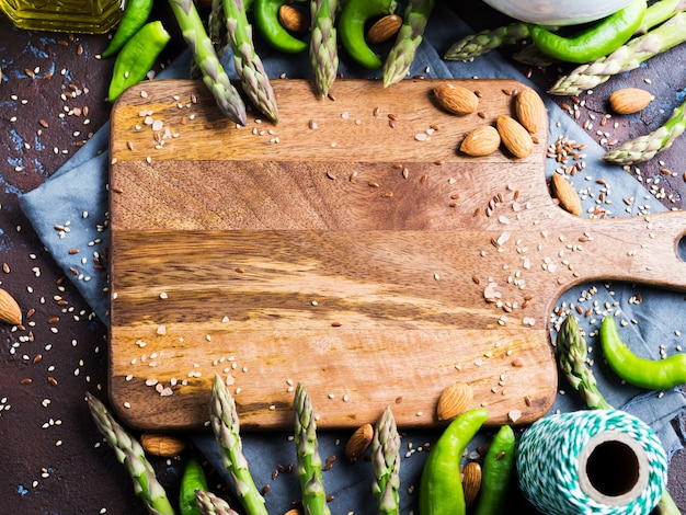 Wooden chopping board with asparagus, nuts, salt