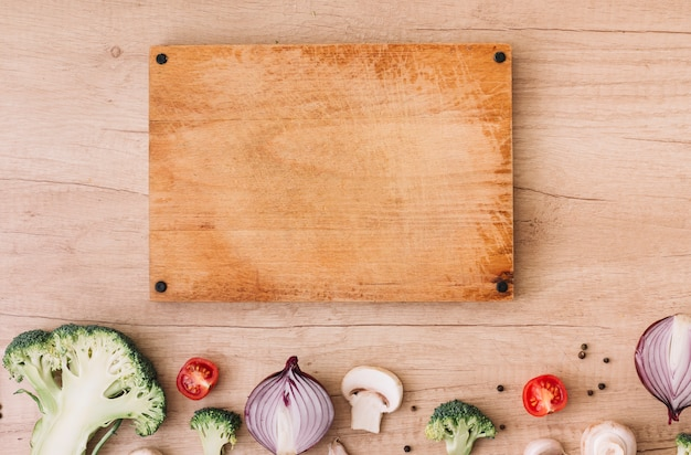 Wooden chopping board with broccoli; tomatoes; onion; mushroom and black pepper on table
