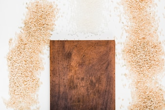 Wooden chopping board with variety of uncooked rice against white background