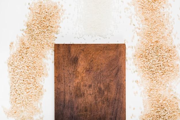 Деревянная разделочная доска с разнообразием сырого риса на белом фоне