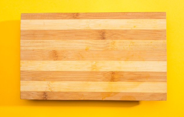 Wooden chopping board on yellow background