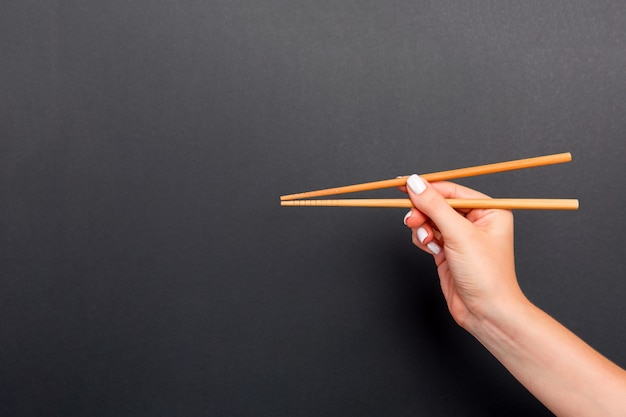 Wooden chopsticks in female hand on black background with empty space for your idea. tasty food concept