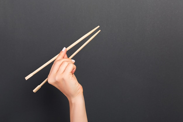 Wooden chopsticks in female hand and black background