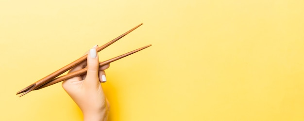 Wooden chopsticks in female hand on yellow surface with empty space for your idea