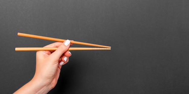 Wooden chopsticks in female hand