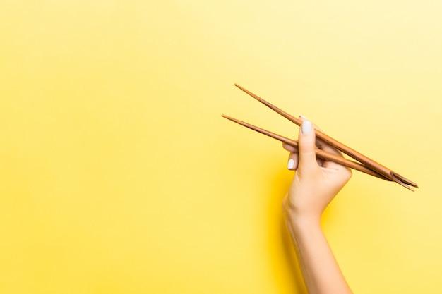 あなたのアイデアのための空のスペースで黄色の背景に女性の手で木製の箸。おいしい食べ物のコンセプト