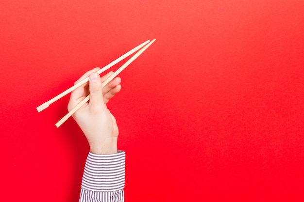 Wooden chopsticks in male hand on red with empty space for your idea.