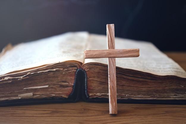 Деревянный христианский крест на библии над деревянным столом