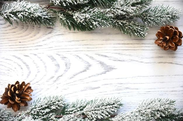 雪に覆われたモミの木の枝と円錐形の木製のクリスマスの背景フレーム