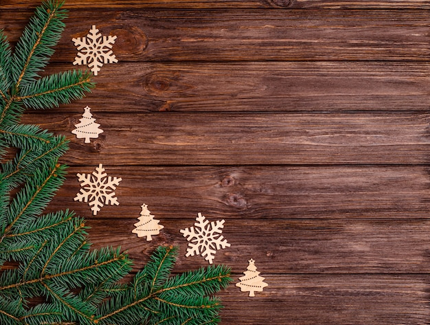 Деревянный новогодний фон с еловыми ветками, деревянными декоративными игрушками. баннер, форма для открытки, поздравления. копирование пространства, плоская планировка. вид сверху