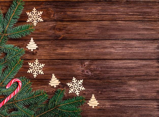 Деревянный новогодний фон с еловыми ветками, деревянными декоративными игрушками, рождественскими конфетами.