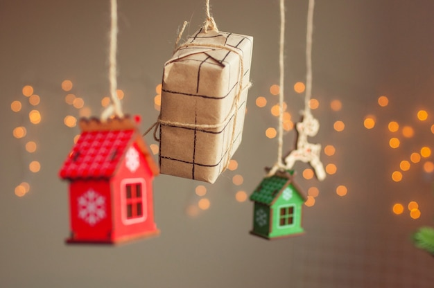 Wooden christmas decoration and craft paper wrapping gift box hanging on the cord on light bokeh background. selective focus on the gift box.