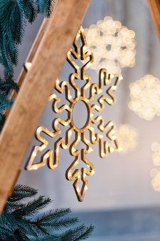 Wooden christmas decoration for the walls. glowing snowflakes with garland lights on gray concrete.