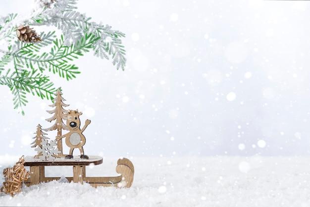雪の上のモミの木と木製のクリスマス鹿。クリスマスや新年のコンセプト