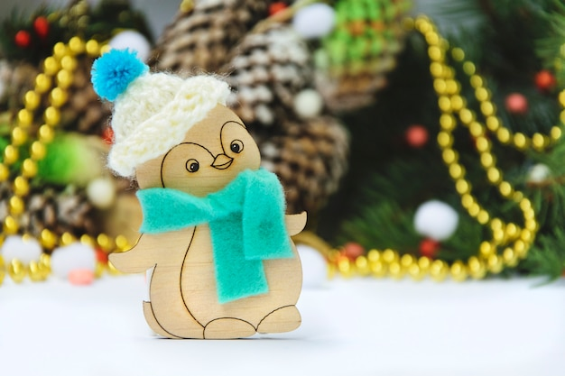 Wooden christmas toy penguin in a hat on a thematic background