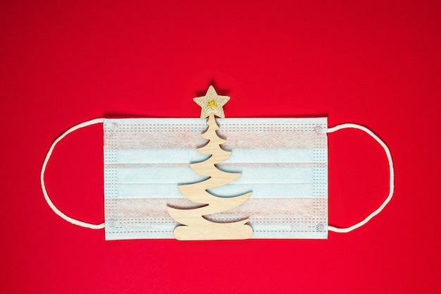 Деревянная елочная игрушка ель на защитной маске от коронавируса. коронавирус рождественский фон. рождество или новый год концепция. плоская планировка