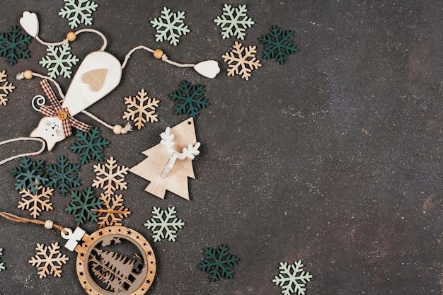 Деревянные елочные игрушки и снежинки на темно-сером фоне.