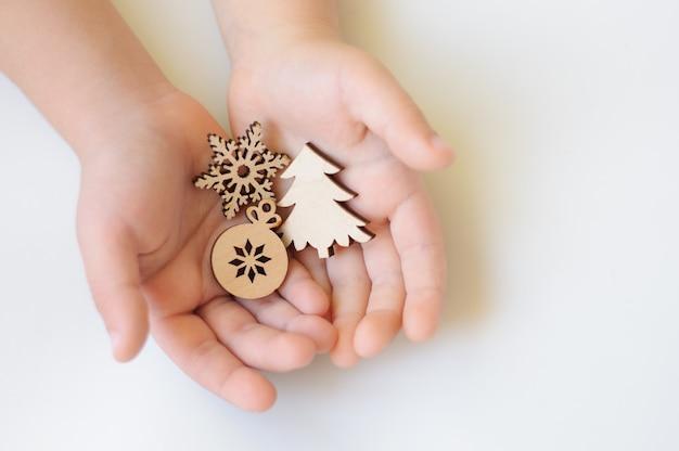 白い背景の上の子供の手の木製のクリスマスのおもちゃ