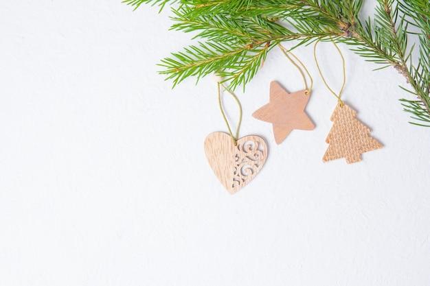 Деревянные елочные игрушки в форме сердца и звезд на гребаном фоне, еловые ветки и экологически чистые елочные игрушки, место для копирования сверху