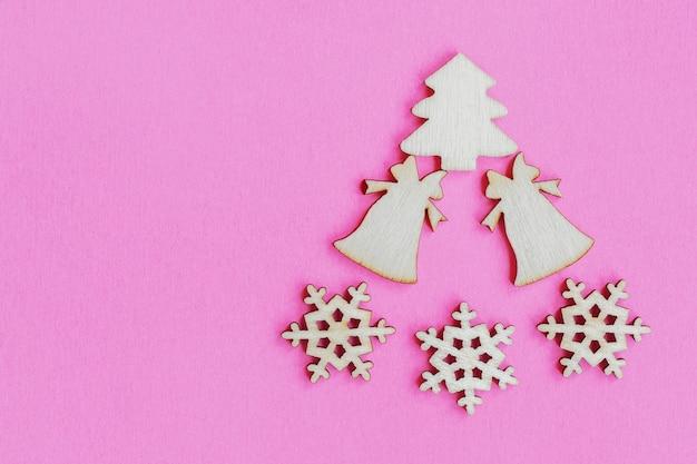 ピンクの背景、平面図、フラットレイ、最小限の新年のコンセプト、デザイン、モックアップまたはポストカードの木製のクリスマスのおもちゃ
