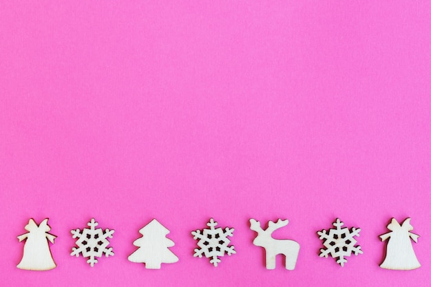 Wooden christmas toys on pink background, top view, flat lay, minimal new year concept, for design, mockup or postcard