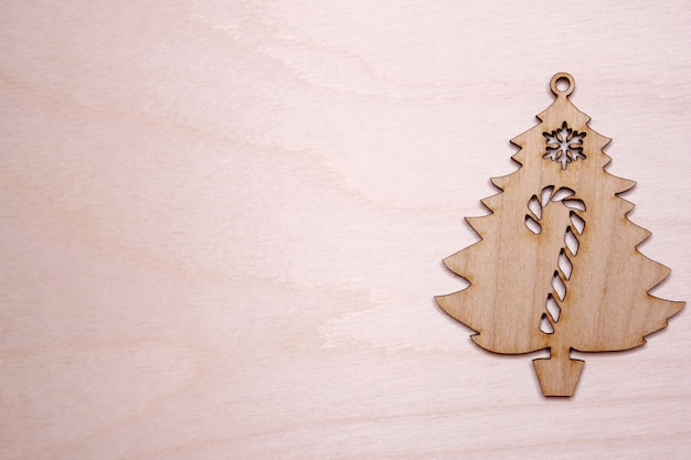 Wooden christmas tree figurine on a wooden background. copyspace.