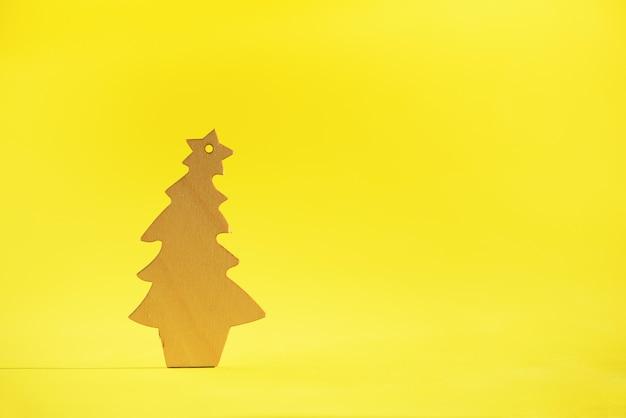 Деревянная рождественская елка на желтом фоне с копией пространства. новогодняя вечеринка.